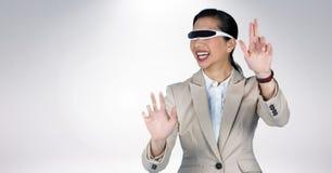 Gestikulierende Geschäftsfrau bei der Anwendung des Kopfhörers der virtuellen Realität Stockbilder