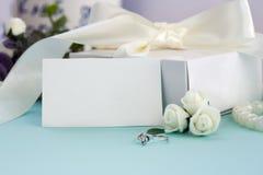 Gestileerde voorraadfoto Het vrouwelijke model van de huwelijksdesktop De witte rozen, doos met een boog, verlovingsring, parelt  royalty-vrije stock afbeelding