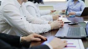 Gestione della società che si siede alla tavola nella riunione d'affari, passante i grafici al capo stock footage