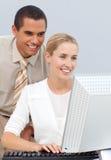 Gestionnaire aidant une femme d'affaires avec son ordinateur photo libre de droits
