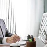 Gestionnaire au travail La main experte d'un homme d'affaires s'asseyant à son bureau, il tient le stylo devant son moniteur d'or photo stock