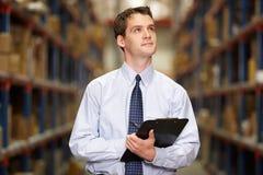 Gestionnaire dans l'entrepôt avec le presse-papiers Photo stock
