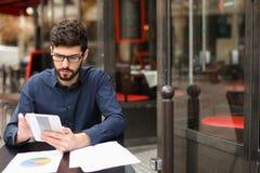 Gestionnaire de comptes frais travaillant avec les papiers et le comprimé à l'étiquette de café photo libre de droits