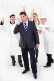 Gestionnaire de restaurant avec le personnel fou derrière Photographie stock libre de droits
