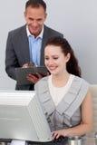 Gestionnaire de sourire contrôlant le travail des ses employés image stock