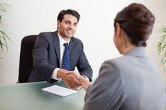 Gestionnaire de sourire interviewant un demandeur féminin images stock