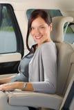 Gestionnaire exécutif de femme s'asseyant dans la banquette arrière de véhicule Photo stock