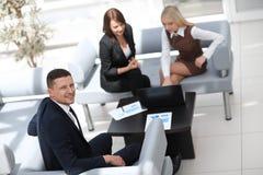 Gestionnaire financier s'asseyant à côté des collègues et regardant l'appareil-photo image stock