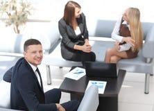 Gestionnaire financier s'asseyant à côté des collègues et regardant l'appareil-photo photo stock