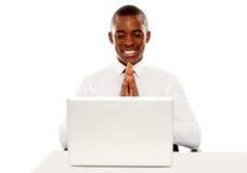Gestionnaire gai regardant l'écran d'ordinateur portatif photo stock