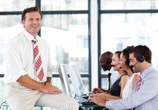 Gestionnaire mûr de sourire à un centre d'attention téléphonique Images stock