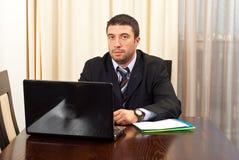 Gestionnaire sérieux avec l'ordinateur portatif images stock
