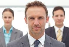 Gestionnaire sérieux posant devant ses collègues Image stock