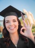 Gesto ACEPTABLE graduando a la mujer de la raza mixta en casquillo y vestido Fotografía de archivo