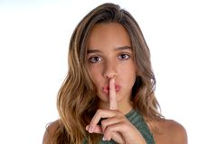 Gesto adolescente moreno del finger del silencio de la muchacha en blanco Imagenes de archivo