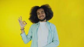 Gesto afroamericano atractivo sonriente de la autorización de la demostración del individuo mientras que se coloca aislado sobre  almacen de metraje de vídeo