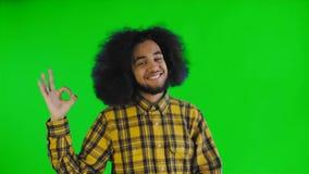 Gesto afroamericano atractivo sonriente de la autorización de la demostración del individuo mientras que se coloca aislado sobre  metrajes