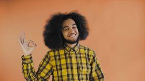 Gesto afroamericano attraente sorridente di approvazione di rappresentazione del tipo mentre stando isolato sopra fondo arancio C archivi video