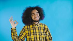 Gesto afroamericano attraente sorridente di approvazione di rappresentazione del tipo mentre stando isolato sopra fondo blu Conce archivi video