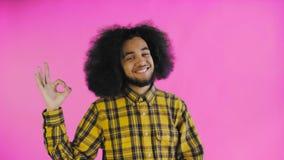 Gesto afroamericano attraente sorridente di approvazione di rappresentazione del tipo mentre stando isolato sopra fondo porpora C video d archivio