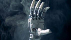 Gesto aprovado de um braço cybernetic nas nuvens de fumo video estoque