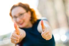 Gesto atractivo con los fingeres - pulgar de la demostraci?n de la mujer para arriba foto de archivo libre de regalías