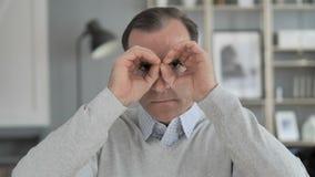 Gesto binocular feito a mão pelo homem envelhecido médio que procura a possibilidade nova vídeos de arquivo