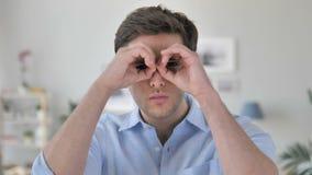 Gesto binocular feito a mão pelo homem novo considerável que procura a possibilidade nova filme