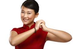 Gesto chino del saludo de la mujer en vestido rojo elegante foto de archivo
