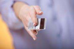 Gesto de ofrecimiento con una tarjeta Fotografía de archivo libre de regalías