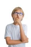 Gesto de pensamiento del niño aislado en el fondo blanco Retrato del muchacho con los vidrios que llevan la camiseta blanca Imagen de archivo