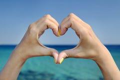 Gesto del cuore della mano del mare di amore Fotografia Stock