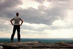 Gesto del triunfo Caminante feliz en greyshirt y trousars oscuros Hombre alto en el pico del acantilado de la piedra arenisca que Fotografía de archivo
