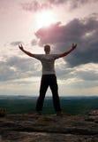 Gesto del triunfo Caminante feliz en greyshirt y trousars oscuros Hombre alto en el pico del acantilado de la piedra arenisca que Fotografía de archivo libre de regalías