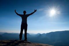 Gesto del triunfo Caminante feliz en ropa de deportes El hombre alto en el pico de la roca de la piedra arenisca en el reloj de S foto de archivo libre de regalías