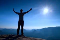 Gesto del triunfo Caminante feliz en ropa de deportes El hombre alto en el pico de la roca de la piedra arenisca en el reloj de S Fotografía de archivo libre de regalías