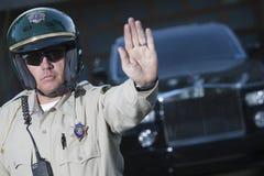 Gesto di arresto di segnalazione del poliziotto di traffico con l'automobile nel fondo Fotografie Stock Libere da Diritti