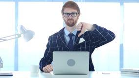 Gesto di Doing Thumbs Down dell'uomo d'affari della testarossa sul lavoro Immagini Stock