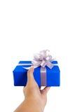 Gesto di mano che dà un regalo avvolto in blu Fotografia Stock Libera da Diritti