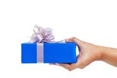 Gesto di mano che dà un regalo avvolto in blu Fotografia Stock
