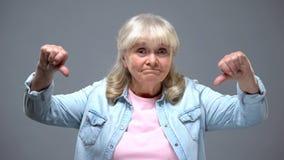 Gesto di mostra femminile anziano divertente dei pollici-gi?, insoddisfatto del governo statale fotografia stock