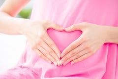 Gesto do amor da mostra da mulher gravida fotografia de stock