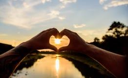 Gesto do coração na frente do por do sol acima de superfície da água do rio, defocused Lugares superiores para a data romântica M imagem de stock royalty free