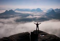 Gesto do triunfo Caminhante feliz no preto Homem alto no pico da rocha do arenito em Suíça de Saxony do parque nacional acima do  Imagem de Stock Royalty Free