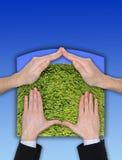Gesto ecologico della casa della mano sul cielo blu Immagini Stock