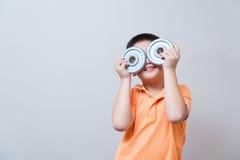 Gesto humorístico del muchacho asiático que lleva los vidrios falsos hechos con dum del hierro Imagen de archivo