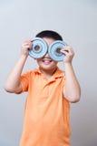 Gesto humorístico del muchacho asiático que lleva los vidrios falsos hechos con dum del hierro Foto de archivo
