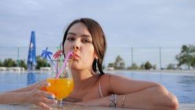 Gesto positivo di giovane bevanda colorata bevente femminile nella piscina all'aperto archivi video