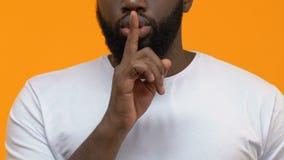 Gesto secreto de la demostración masculina barbuda joven, sosteniendo el finger cerca de los labios, silencio almacen de metraje de vídeo