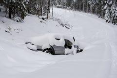 Gestohlenes und mit einem Graben umgegebenes Auto im Winter umfasst mit starker Schicht sno Lizenzfreie Stockbilder